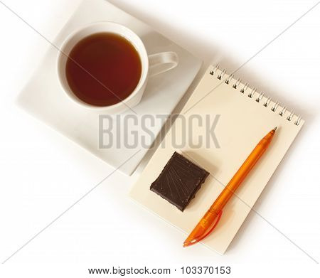 A notepad with a bright pen, a cup of tea and a slice of chocolate on a white background