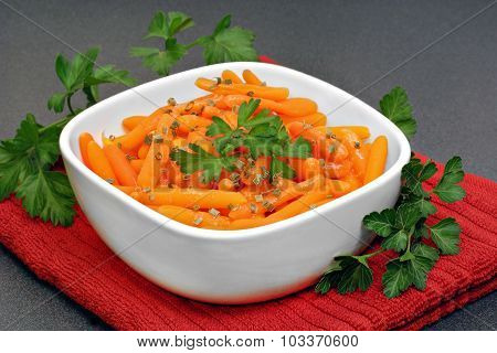 Baby Carrots Garnished With Parsley In A White Bowl.