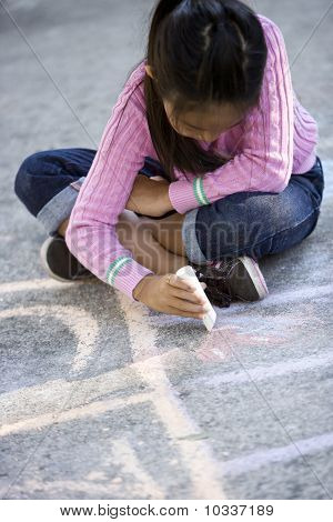 Asian Girl Drawing On Ground With Sidewalk Chalk