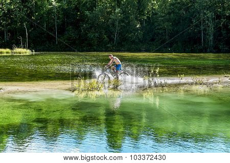 Cyclist Rides A Bicycle Across The River
