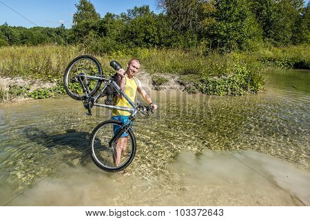 Cyclist Holding His Bicycle, Standing In A River