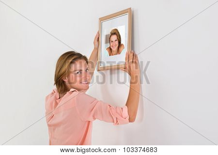 Happy Woman Putting Picture Frame On Wall