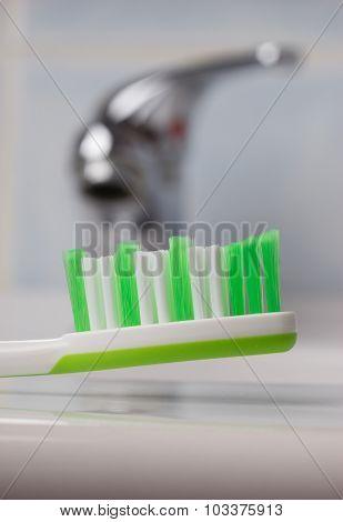 Green Toothbrush In Bathroom On Sink
