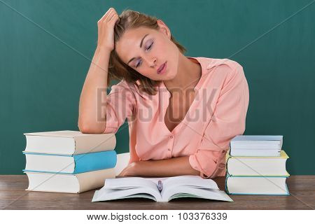Tired Female Teacher With Books