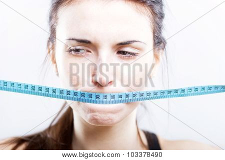Woman With Measuring Tape Covering Her Mouth