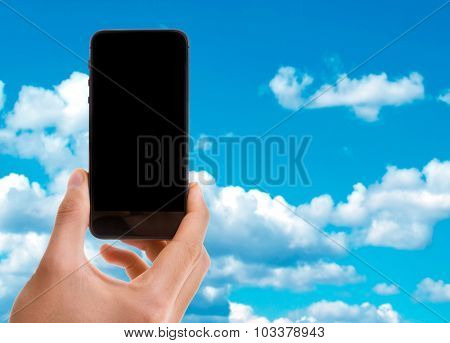 Hand holding mobile with black screen on sky background