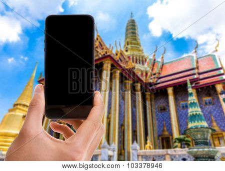 Hand holding mobile with black screen on Thailand Temple background