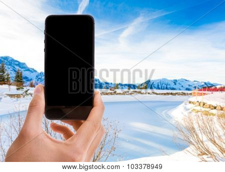 Hand holding mobile with black screen on Switerland background