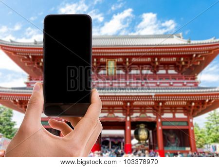 Hand holding mobile with black screen on Japan temple background