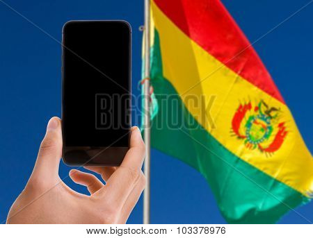 Hand holding mobile with black screen with Bolivia Flag background