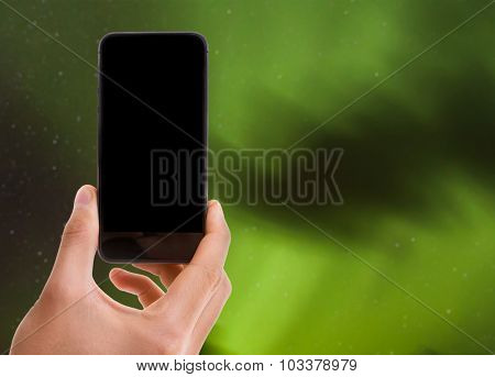 Hand holding mobile with black screen on Northern Lights background