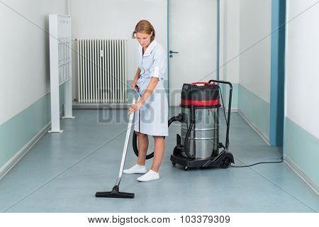 Female Cleaner Vacuuming Floor