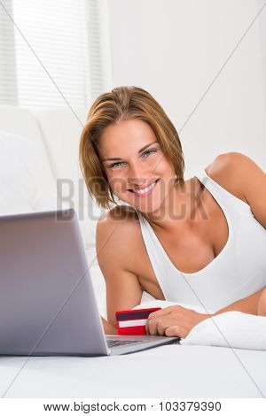 Woman With Laptop And Credit Card In Bedroom