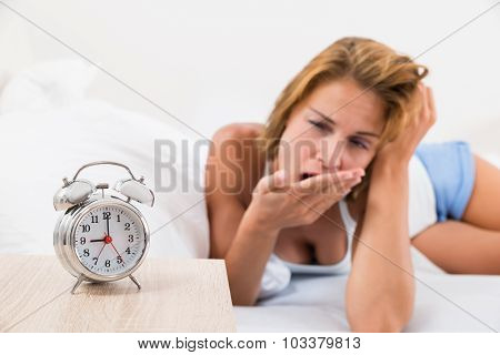 Woman With Alarm Clock On Nightstand