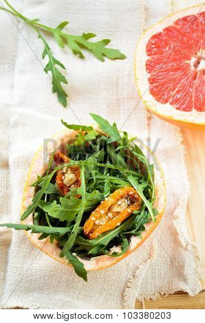 salad with rucola, sun-dried tomatoes and sesame in grapefruit