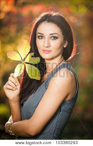Beautiful woman in gray posing in autumnal park. Young brunette woman holding a leaf