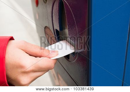 Person Hands Inserting Ticket Into Parking Machine