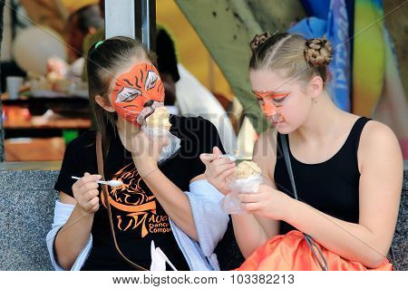 two girls with narisoval tiger mask on his face eating ice cream
