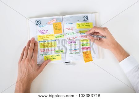 Businessperson Writing Note In Diary