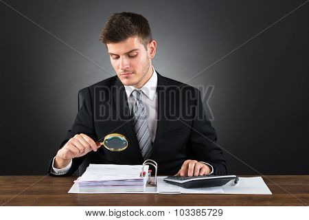 Businessman Scrutinizing Invoice