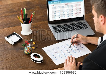 Businessman Marking Date On Calendar