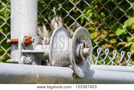 Worn Metal Roller On Fence Frame With Rusted Screw