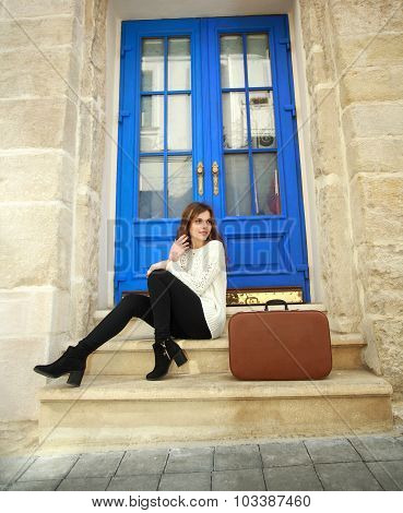 Woman traveler with a suitcase sitting dreamy at her house