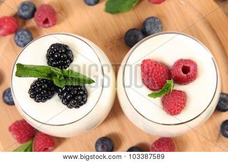 sweet berries with yogurt on wooden table