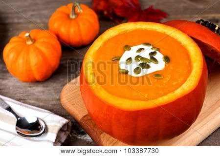 Creamy autumn soup in pumpkin bowl