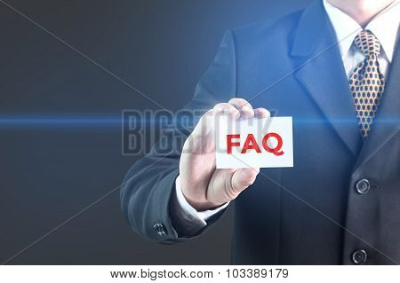 A Businessman holding a white sign with the message faq.