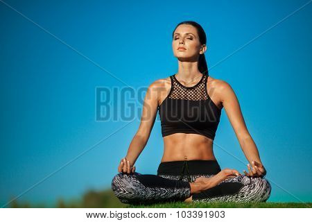 Attractive young woman in a lotus position in green park