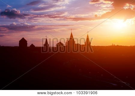 Cloudy Sunset view on the old Ancient stone castle silhouette and road