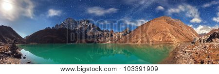 Beautiful turquoise lake high in the mountains under blue sky with white clouds