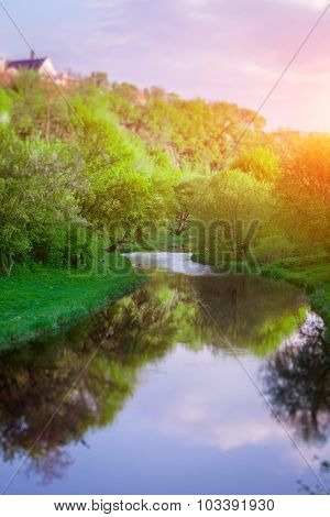 Small calm river with reflection among fresh green grass, trees and bushes