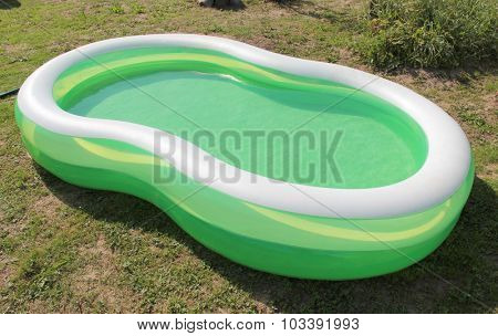 Inflatable pool with water on green grass