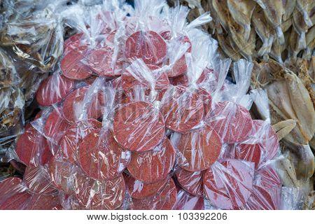 Shrimp Paste Inside Plastic Sandwich Between Outfocus Salted Fish On Market Display.