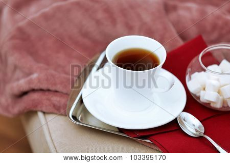 Cup of tea on sofa in living room
