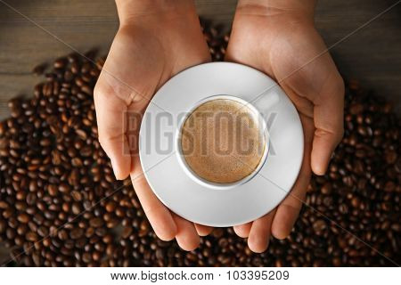 Female hands holding cup of coffee with foam over grains, top view