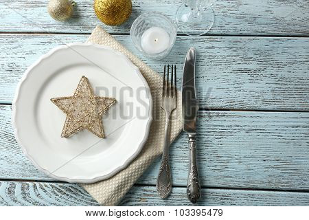 Empty plate, cutlery, napkin and glass on rustic wooden background. Christmas table setting concept