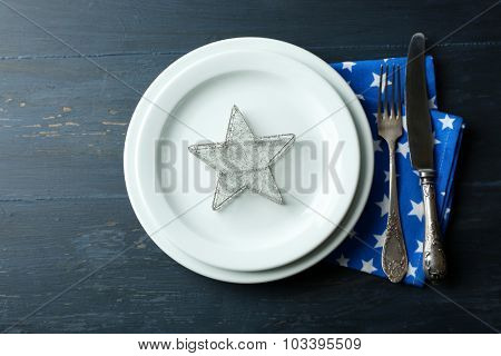 Empty plate, cutlery, napkin on rustic wooden background. Christmas table setting concept