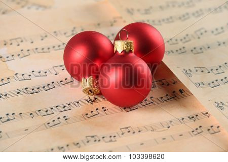 Christmas ball on music sheets background