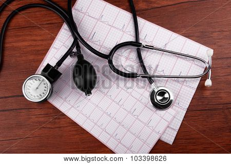 Blood pressure meter and stethoscope, on wooden background