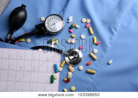 Blood pressure meter, pills and stethoscope, on blue uniform background