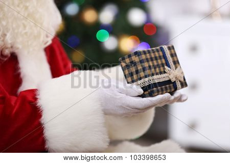 Santa holding gift on Christmas tree background