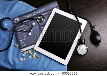 Blood pressure meter, stethoscope, digital tablet on dark background