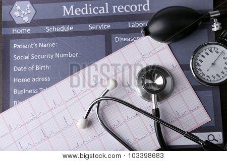 Blood pressure meter and stethoscope, on dark wooden background