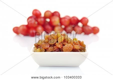 Raisins with grapes in bowl isolate on white