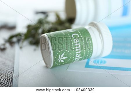 Bottle of dry medical cannabis with clipboard on table close up