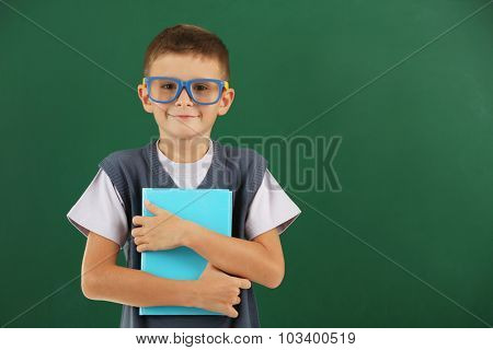 Beautiful little boy on blackboard background