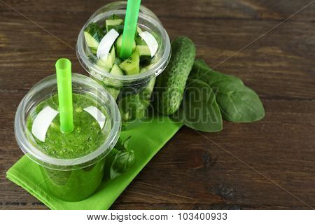 Green vegetable and fruit salad and healthy fresh drink in plastic cups on wooden background. Colorful diet concept